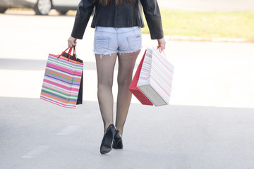 Let's go shopping.  Close-up of 40 yo woman with shopping bags going from the mall