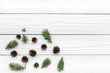 New year symbols pattern. Spruce branches and cones on white wooden background top view copyspace