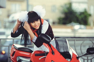 Beautiful young woman, hairstyle and bows outdoors with a motorcycle. Happy and healthy dressed in a Soviet school uniform. girl biker. Concept of fun