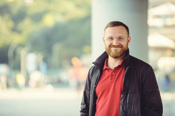 man with a red beard, dressed in a red gaiety in the city. Happy and healthy. looks and mysteriously smiles. Concept idea of success