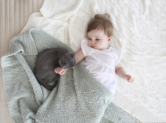 Close up portrait of a beautiful baby with kitten