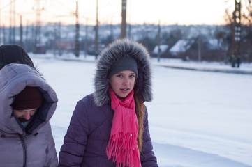 Girls walk in the winter on the street in the snow.