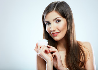 Smiling girl holding beauty skin care cream in glass jar.