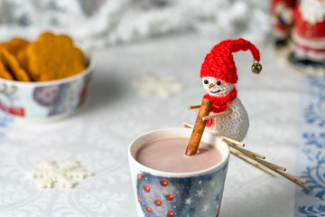 Crocheted snowman stirs cocoa