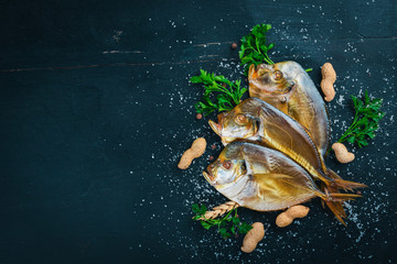 Smoked fish, Vomer. Seafood. On a wooden background. Top view. Free space for your text.
