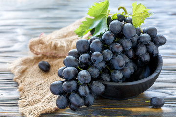 Delicious black grapes in a wooden bowl.