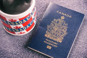 Canadian passport sitting next to a canada mug