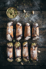 Homemade cannoli dessert with pistachios on wooden background