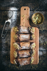 Homemade cannoli with pistachios served on the wooden board