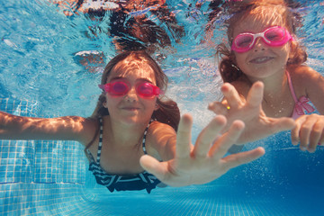 Two happy girls in goggles swimming under water
