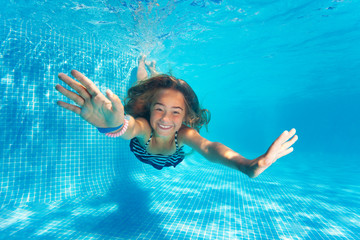 Portrait of preteen girl diving with fun in pool