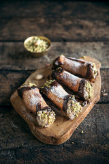 Homemade cannoli with pistachios served on the wooden background,selective focus
