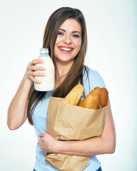 woman holding paper bag with bread and milk bottle.
