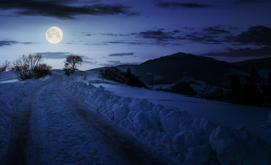 countryside road uphill in snow at night in full moon light. beautiful winter scenery in mountainous area