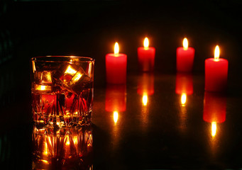 christmas decoration with glass of whiskey or cognac and red candles on a wooden background. Selective focus.