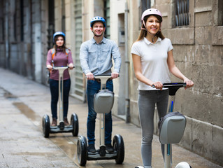 Positive friends posing on segways in vacation