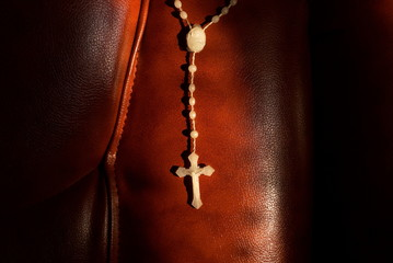 white rosary on a leather red sofa