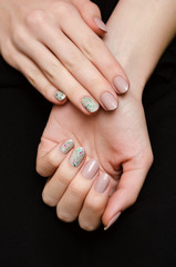Female hands with beige glitter nail design