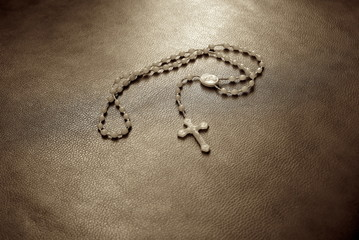 white rosary on a leather sofa