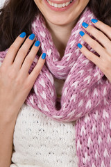 Portrait of young woman with beautiful blue nail Polish in knitted scarf. Hands with beautiful manicure closeup