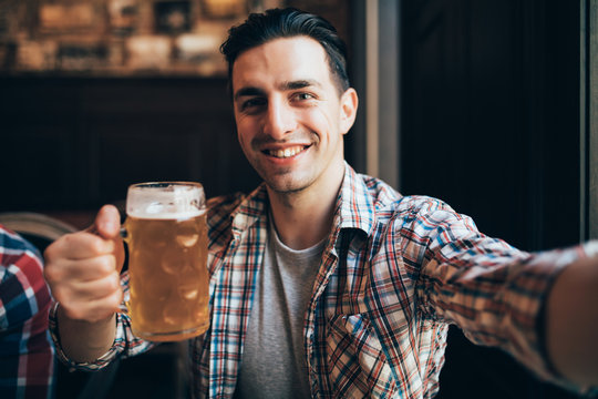 Shot of an excited young man screaming happily taking a selfie with a glass of beer relaxing at the local pub