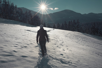 Sunny winter day with woman walks in the fresh snowy landscape.