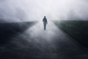 Man walking alone on dark misty foggy asphalt road.  Wall mural