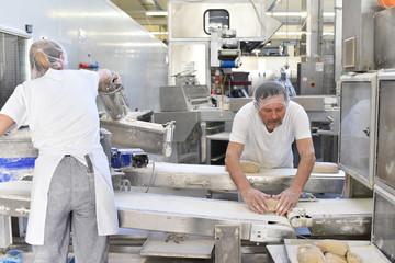 Großbäckerei - Herstellung von Brot - Bäcker und Mitarbeiterin am Fliessband kneten Teig // Large bakery - production of bread - baker and employee knead dough on a conveyor belt