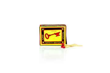 A vintage match box with swastikas and a key  on the front. Isolated studio shot on white background.