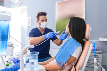 A young Dentist treating a female Patient in the dental studio