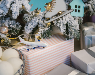 Toy airplane among Christmas decorations and boxes. Give a trip is the best gift. Home party cozy moment.