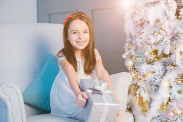 Kid girl opening Christmas presents. Stylish New Year decoration interior. Home cozy mood