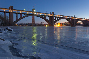 Evening view of arched bridge over the frozen Dnieper river in Zaporozhye, Ukraine