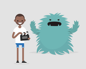 Film set. Horror movie. Big scary monster. Young black character holding a retro clapper board. Entertainment industry / flat editable vector illustration, clip art