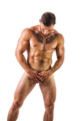 Apparently naked male bodybuilder hiding genitals with hands, looking down, isolated on white background