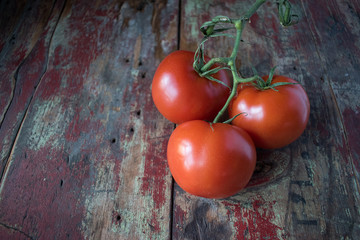 three red ripe tomatoes on vine in rustic setting