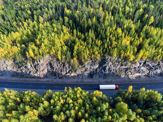 Top view at white semitrailer truck driving between rock tunnel in autumn forest of Karelia, Russia