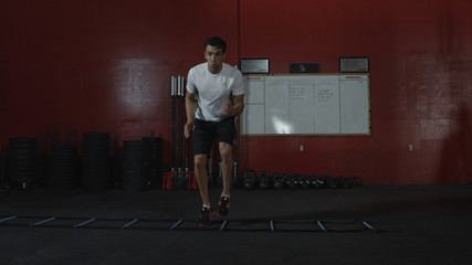 Athletic man does side step ladder exercise in gym