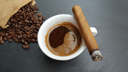 Coffee cup, beans and cigar  on dark  background