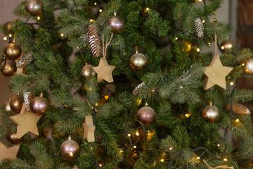 Christmas tree with wooden rustic decorations. Dark loft interior.