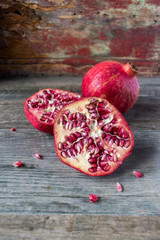 pomegranates sliced and whole on rustic table