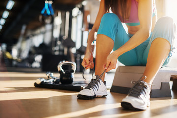 Close up of young slim fitness girl sitting on the stepper and tying shoelaces in the gym.