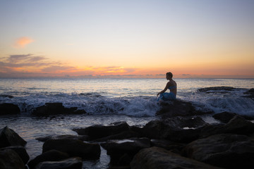 Thoughtful woman sitting on rock at beach during sunset