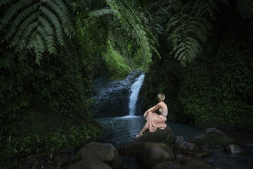 woman sitting in front of waterfall oasis