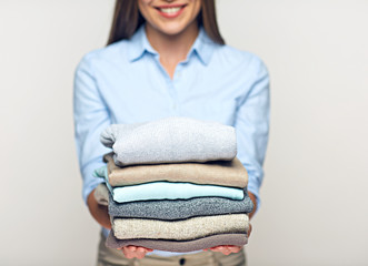 Woman holding stack of folded sweaters.
