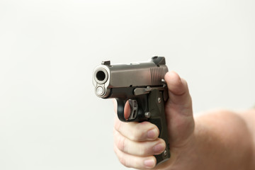 unknown hand holding semi auto pistol