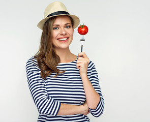 Smiling woman holding tomato on fork.
