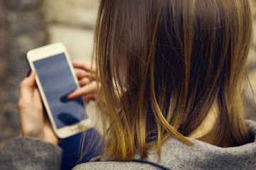 Social Media addiction. Young beautiful woman holding a smartphone (psychological problems, media mania concept)