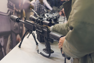 Man with an automatic rifle at the store counter. Weapons