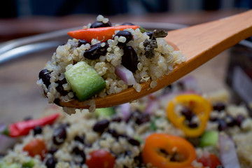 Spoon full with quinoa and black bean salad for weight loss- Quinoa is a pseudo-grain that has all nine essential amino-acids